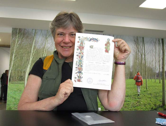 Anne Born receiving her latest Compostela in the Pilgrim Office of Santiago